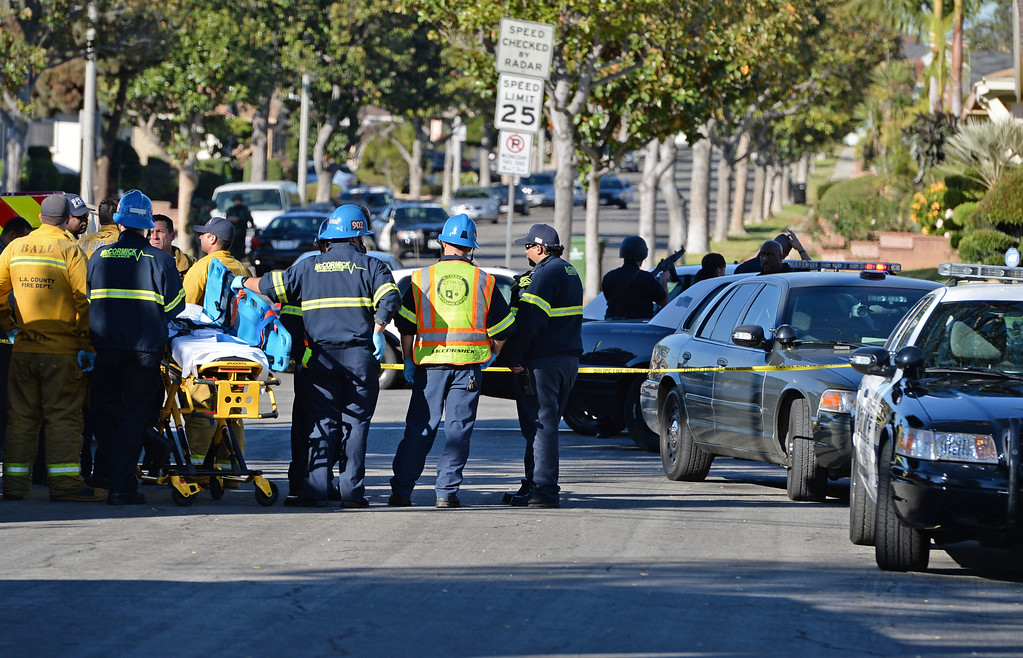 . A man allegedly shot an Inglewood police officer Wednesday, November 27, 2013, in Inglewood, CA, and the took hostages as he barricaded inside a house on S. 5th Avenue.  Medics stand at the ready a block from the shooting. Photo by Steve McCrank/DailyBreeze
