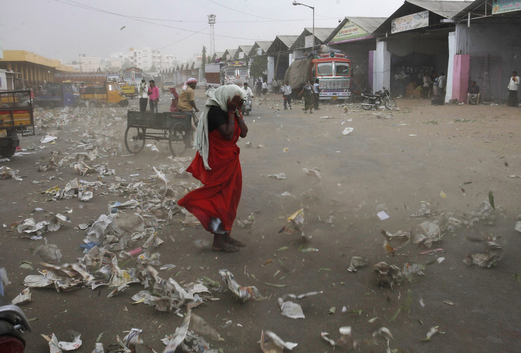 Description of . An Indian woman tries to shield herself from the wind in Hyderabad, India, Tuesday, April 2, 2013. (AP Photo/Mahesh Kumar A.)