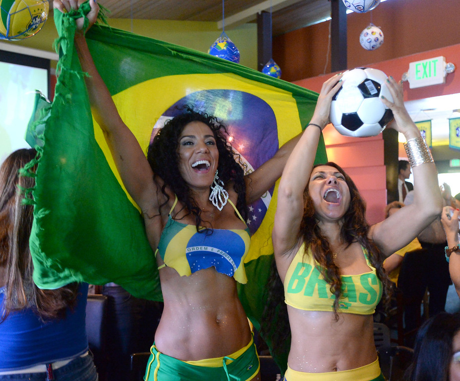 . Brazil soccer fans Marisa Cortez, left, and Katia Neves, right, cheer as Brazil scores against Croatia. Fans crowded into Samba restaurant to watch the FIFA World Cup game against Croatia Thursday, June 12, 2014, Redondo Beach, CA.  The South Bay is home to a large Brazilian community. Photo by Steve McCrank/Daily Breeze