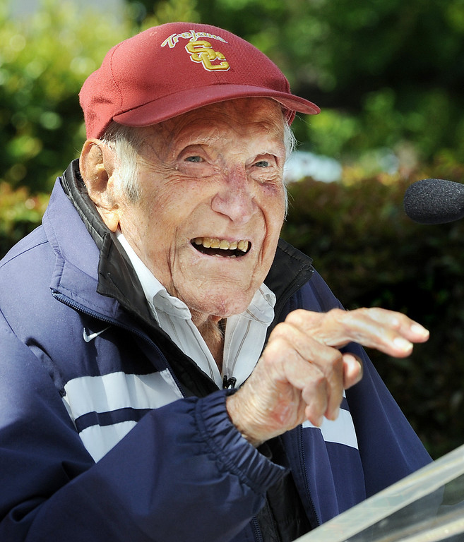 Description of . Louis Zamperini,  who was a student and track star at USC, asking audience if they knew what hand gesture meant,