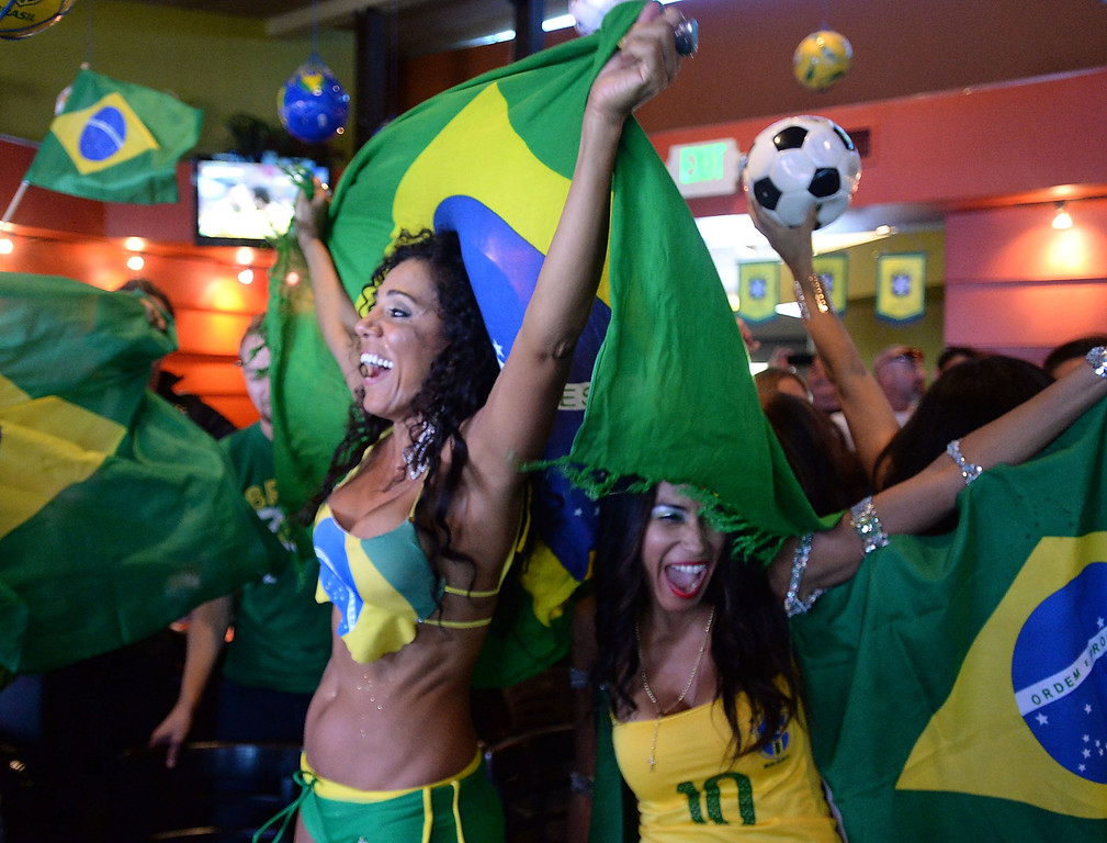 . Brazil soccer fans Marisa Cortez, left, and Joany Macias, right, cheer as Brazil scores against Croatia. Fans crowded into Samba restaurant to watch the FIFA World Cup game against Croatia Thursday, June 12, 2014, Redondo Beach, CA.  The South Bay is home to a large Brazilian community. Photo by Steve McCrank/Daily Breeze