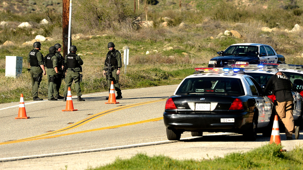 . A SWAT team stands guard at a blockade at Highway 38 and Bryant Street near the Mill Street Ranger Station west of Yucaipa February 12, 2013.   Authorities believe that they exchanged gunfire with fugitive Christopher Dorner in the Angles Oaks area of the San Bernardino National Forest.  Fish and Game officers spotted a man fitting the description of Dorner driving a white pick-up, and two San Bernardino County Sheriff Deputies exchanged gunfire with him.  Authorities believe Dorner is holed up in a cabin on Glass Road and Highway 38.  GABRIEL LUIS ACOSTA/STAFF PHOTOGRAPHER.