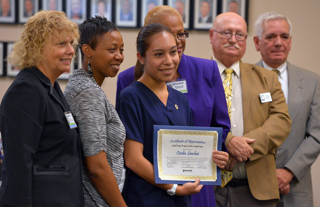 . Cindia Sanchez stands with teachers and Goodwill staff as she and nine other recent high school graduates received their Certified Nursing Assistant certificates at the Goodwill in Long Beach, CA on Friday, August 22, 2014. The students; Gabriela Avila, Averianna Burnett, Alesia Clay, Ariana Mays, Kendra Montano, Silvia Monzon, Genesis Perez, Cindia Sanchez, Daniel Scott and Dahlia You completed the year-long course in a partnership between the LBUSD and Goodwill. This is the first year that the state Certified Nurse Assistant Training Academy program has been free for the students. It was announced to the families and friends gathered that all 10 of the graduates have health care job interviews next week. (Photo by Scott Varley, Daily Breeze)