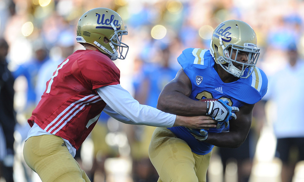 Description of . UCLA quarterback Jerry Neuheisel (11) hands-off to running back Malcolm Jones (28) during the football spring showcase college football game in the Rose Bowl on Saturday, April 27, 2013 in Pasadena, Calif.    (Keith Birmingham Pasadena Star-News)