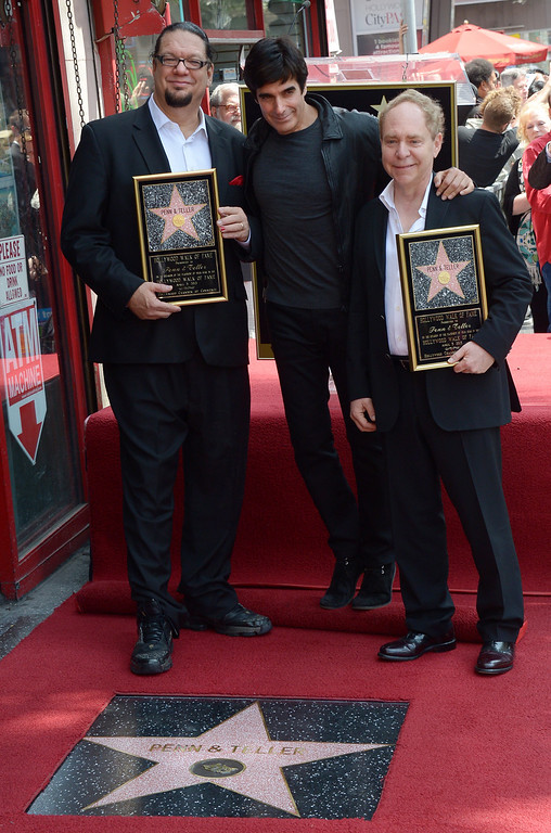 . American illusionists and entertainers Penn Jillette (L) and Teller (R) pose with magician David Copperfield while being honored with a star on the Hollywood Walk of Fame on April 05, 2013 in Hollywood, California. AFP PHOTO/JOE KLAMAR        (Photo credit should read JOE KLAMAR/AFP/Getty Images)