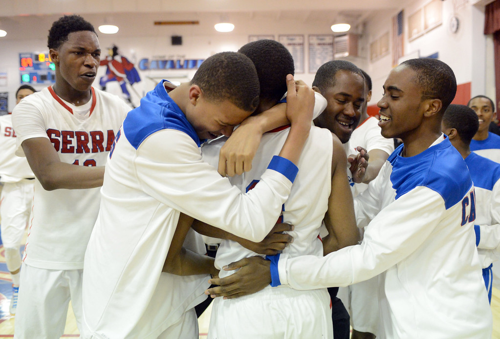 . Serra\'s Jeremy Wright is hugged by teammates after sinking the game winning shot against JSerra in a CIF Division IV-AA quarterfinal game Tuesday night in Gardena. Serra won the game 69-66 on a buzzer beater from Jeremy Wright. 20130219 Photo by Steve McCrank / Staff Photographer