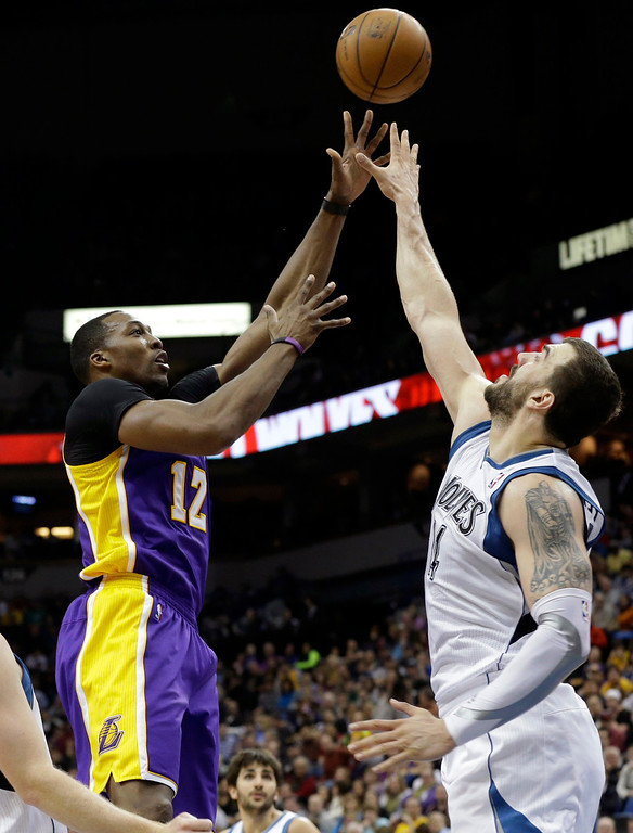 . Los Angeles Lakers\' Dwight Howard shoots the ball over Minnesota Timberwolves\' Nikola Pekovic of Montenegro in the second half of an NBA basketball game Wednesday, March 27, 2013 in Minneapolis. The Lakers won 120-117. (AP Photo/Jim Mone)