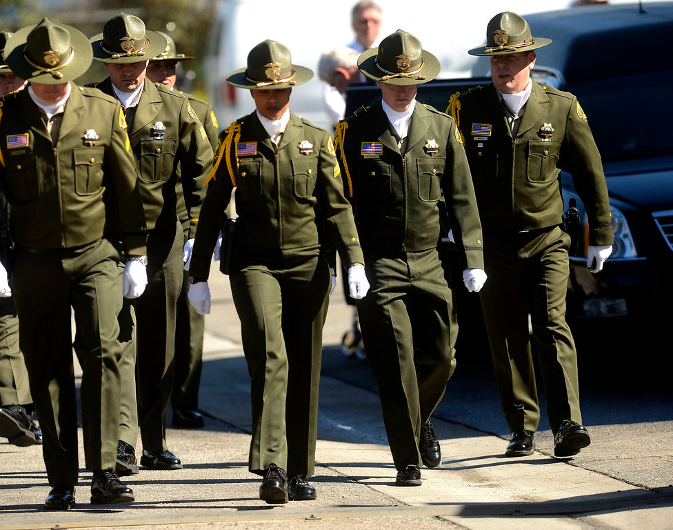. San Bernardino County Sheriff\'s  Deputies walk to their vehicles after the body Jeremiah MacKay was loaded into a hearse at the SBCO Coroner\'s Office in San Bernardino February 14, 2013.  The Department held a small service with Honor Guard, and the playing of bag pipes prior to a procession led by a motorcade to Mountain View Mortuary in San Bernardino.  McKay was the final victim of fugitive Christopher Dorner.   GABRIEL LUIS ACOSTA/STAFF PHOTOGRAPHER.