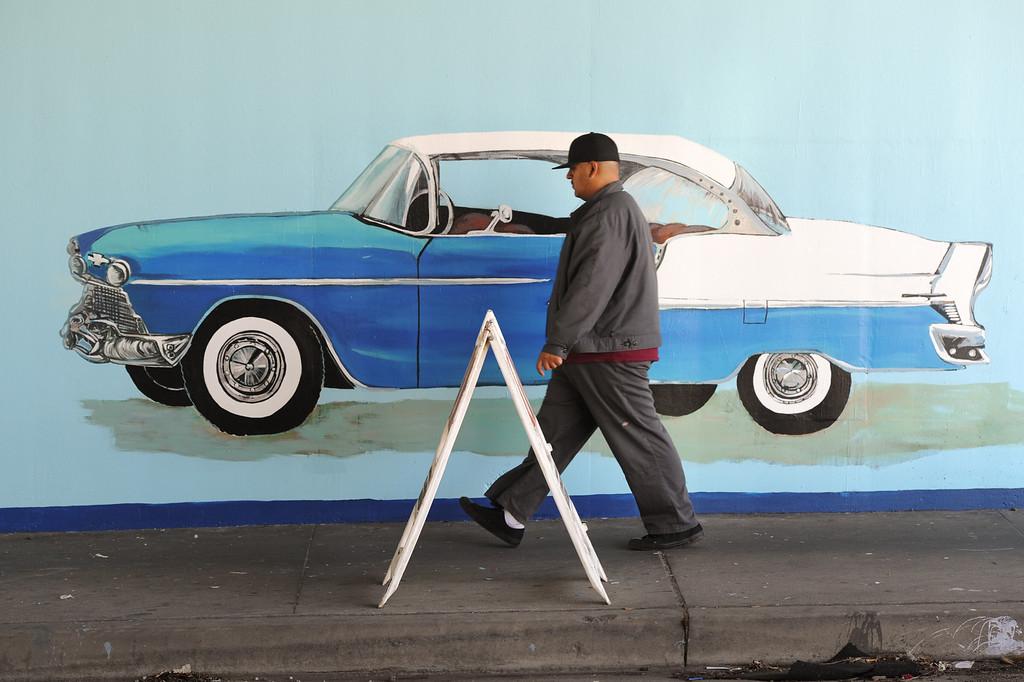 ". A person walks by the restored mural ""Panorama: G.M. Recollections from the Past,\"" on Van Nuys Boulevard in Panorama City. (Michael Owen Baker/Staff Photographer)"