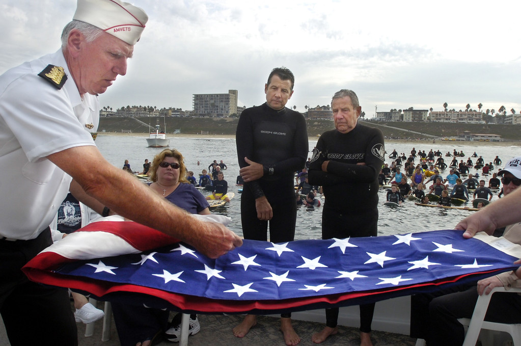 . REDONDO BEACH - 10/01/06 - DAILY BREEZE PHOTO: SCOTT VARLEY - Memorial service for Body Glove co-founder Bill Meistrell off the coast of Redondo Beach. To honor the time he spent in the Army and the war in Korea, AMVETS Legion of Honor member Richard Florence helps fold a flag presented to Billy Meistrell and Bob Meistrell.
