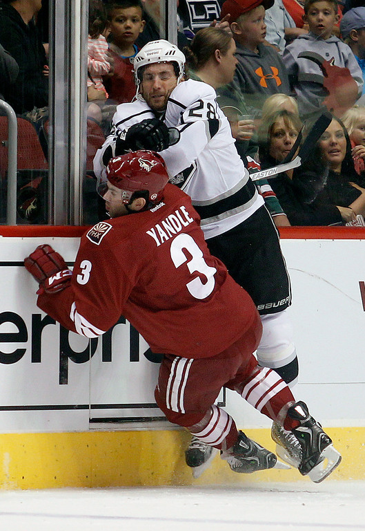 . Phoenix Coyotes defenseman Keith Yandle, left, is checked by Los Angeles Kings center Jarret Stoll, right, in the first period of an NHL hockey game Tuesday, April 2, 2013, in Glendale, Ariz. (AP Photo/Paul Connors)