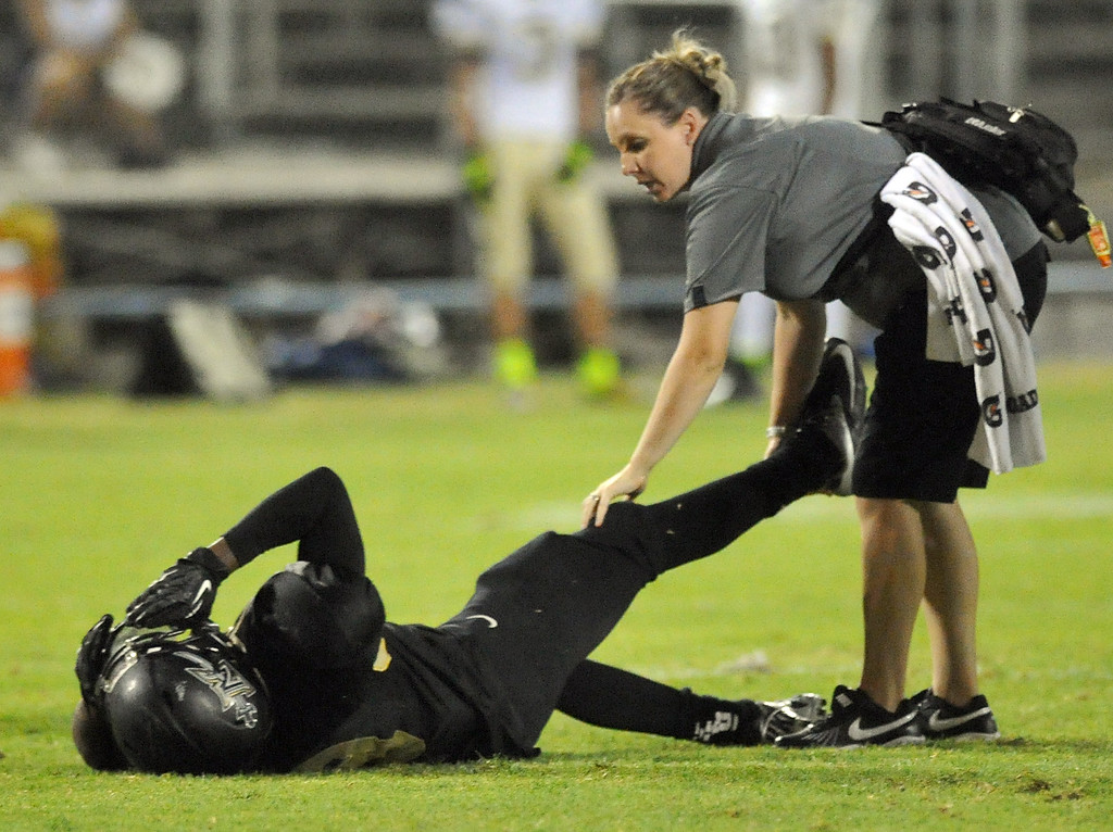 Description of . Northview runningback Christeon Blackmon (#8) reacts in pain as he is tended to by a trainer as they play Rowland in their non-league game at Covina District Field in Covina on Friday September 13, 2013.