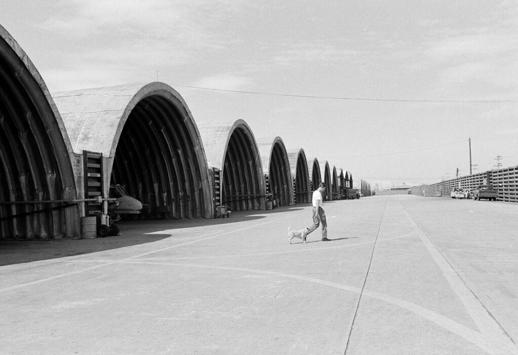 Description of . A U.S. airman, his pet dog following behind him, walks past the quiet and deserted hangars at Da Nang Air Base, Jan. 29, 1973.  Four thousand Americans here are preparing to go home, but this airman's dog will not be allowed to go home with him.  (AP Photo/Dang Van Phuoc)