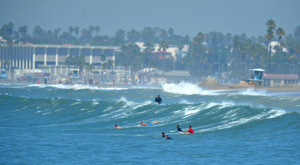 . Surfers ride waves inside the breakwater as high tide and a storm surge from Hurricane Marie had locals bracing for the worst in the Peninsula neighborhood in Long Beach, CA on Wednesday, August 27, 2014. With city crews constantly building a sand berm, the water was held back from the homes and streets during the morning high tide. (Photo by Scott Varley, Daily Breeze)