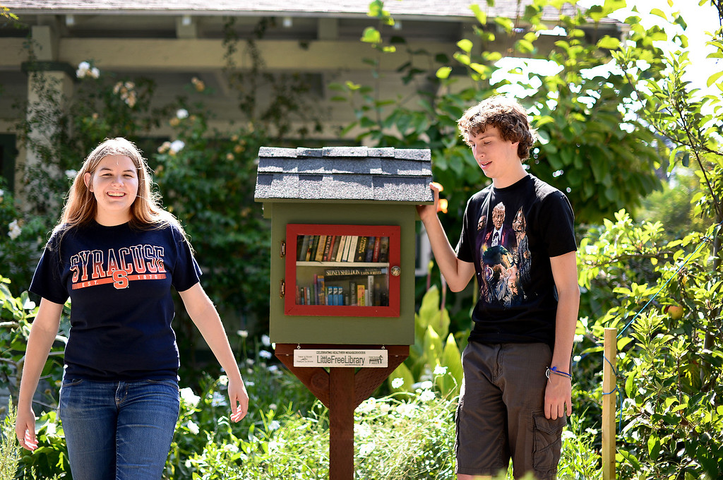 . Stephanie Cox, 18, who created five free neighborhood book nooks in Monrovia for her Girl Scout Gold Award Project, with her friend Travis Stone, 18, visit Stone\'s Little Free Library Friday, July 19, 2013 at his home on Melrose Avenue. (SGVN/Staff Photo by Sarah Reingewirtz)