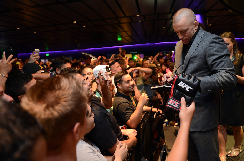 . UFC welterweight champion George St-Pierre signs autographs during the UFC World Tour at Club Nokia Tuesday, July 30, 2013 in Los Angeles. (Hans Gutknecht/Los Angeles Daily News)