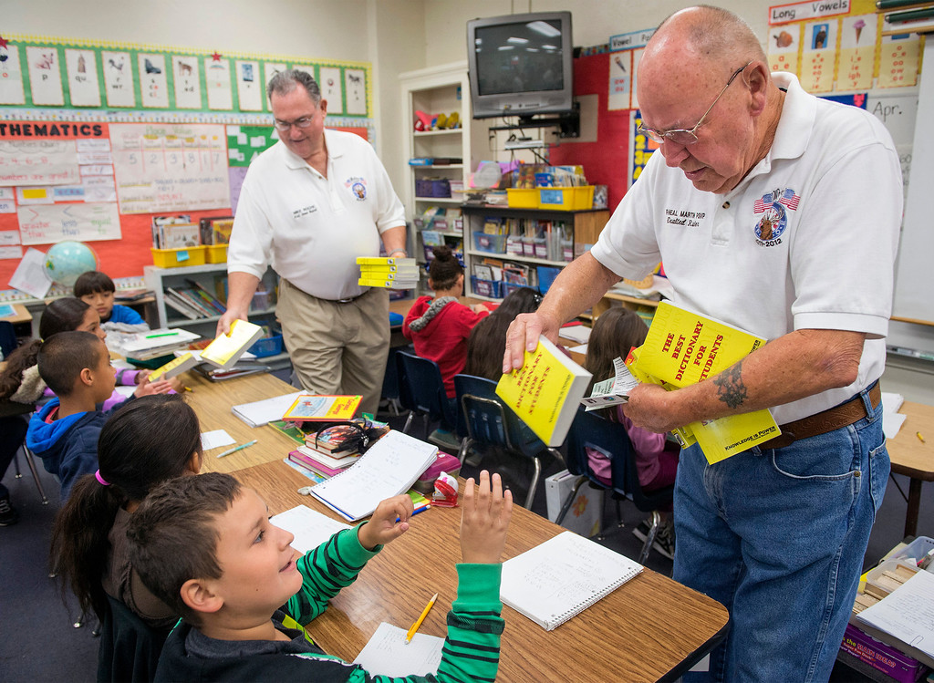Description of . Whittier Elks Lodge #1258 Exalted Ruler Mike Roche, left, and longtime member Neal Martin pass out free dictionaries to Longfellow Elementary School third-graders at the Whittier campus April 8, 2013.  (SGVN/Staff photo by Leo Jarzomb)