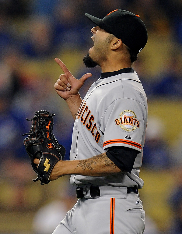 . San Francisco Giants relief pitcher Sergio Romo points to the sky after getting the  final out in the ninth inning of their baseball game against the Los Angeles Dodgers on Wednesday, April 3, 2013 in Los Angeles. San Francisco Giants won 5-3. 