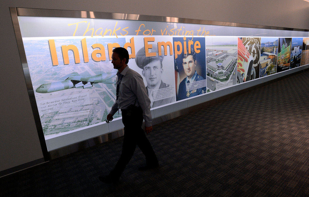 Description of . Airport Manager Scott Gibbs walks past a display of Inland Empire history at the San Bernardino International Airport March 28, 2013.  Built on the former the site of the former Norton Air Force Base, is often described by local officials as one of the East Valley's best hopes for economic growth. Norton closed in 1994.  GABRIEL LUIS ACOSTA/STAFF PHOTOGRAPHER.