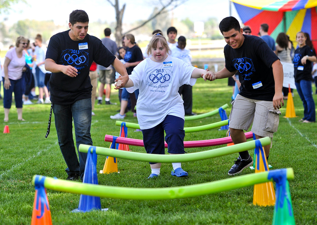 Description of . Student Stacy Shreves participates in the hurdle event with the help of volunteersRainier Aguilar, left, and Belizario Gutierrez, right, at the annual olympic games at Anderson School in San Bernardino on Friday, March 15, 2013. Students with special needs were involved in activities including a relay race, long jump, kickball and more. (Rachel Luna / Staff Photographer)