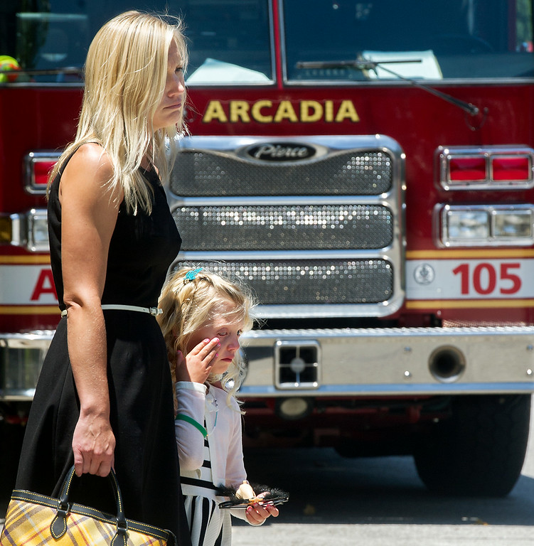 Description of . Brigitte Herdman herdaughter Sienna, who is wiping away tears while watching Michael Herdman coffin being loaded in hurst at memorial service on Wednesday, July 9, 2014, for the Arcadia firefighter-paramedic found dead in the Los Padres National Forest last Friday. Herdman, an avid adventurer, died after becoming separated from his camping partner. He fell from a cliff and was killed by his injuries. Searchers canvassed the forest for 11 days before finding his body.(Photo by Walt Mancini/Pasadena Star-News)