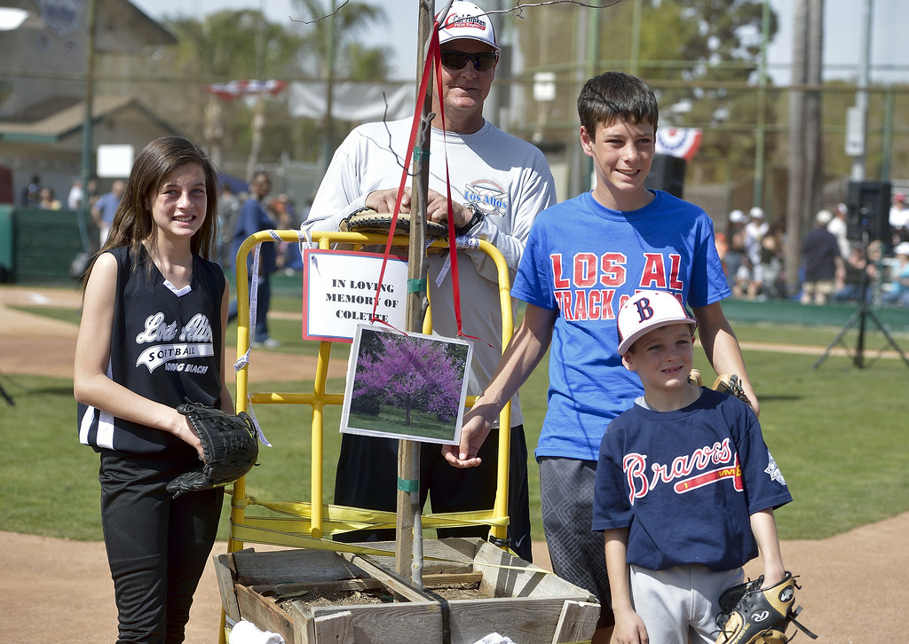 . LONG BEACH, CALIF. USA -- Makayla  Fowler, left, Andrew Fowler, center, and Jacob Fowler and their father, league president Dwayne Fowler, with a tree that was dedicated to their mother, Colette, during opening ceremonies for Los Altos Youth Baseball and Softball at El Dorado Park in Long Beach, Calif. on March 2, 2013. Colette Fowler who was in charge of the snack bar and was a huge part of the league. She died of cancer last September.    hugs his oldest son, Andrew Fowler, after Andrew delivered one of three first pitches during opening ceremonies at El Dorado Park in Long Beach, Calif. on March 2, 2013. Fowler\'s other children, Jacob Fowler and Makayla Fowler delivered the other first pitches. Their mother, Colette Fowler Photo by Jeff Gritchen / Los Angeles Newspaper Group