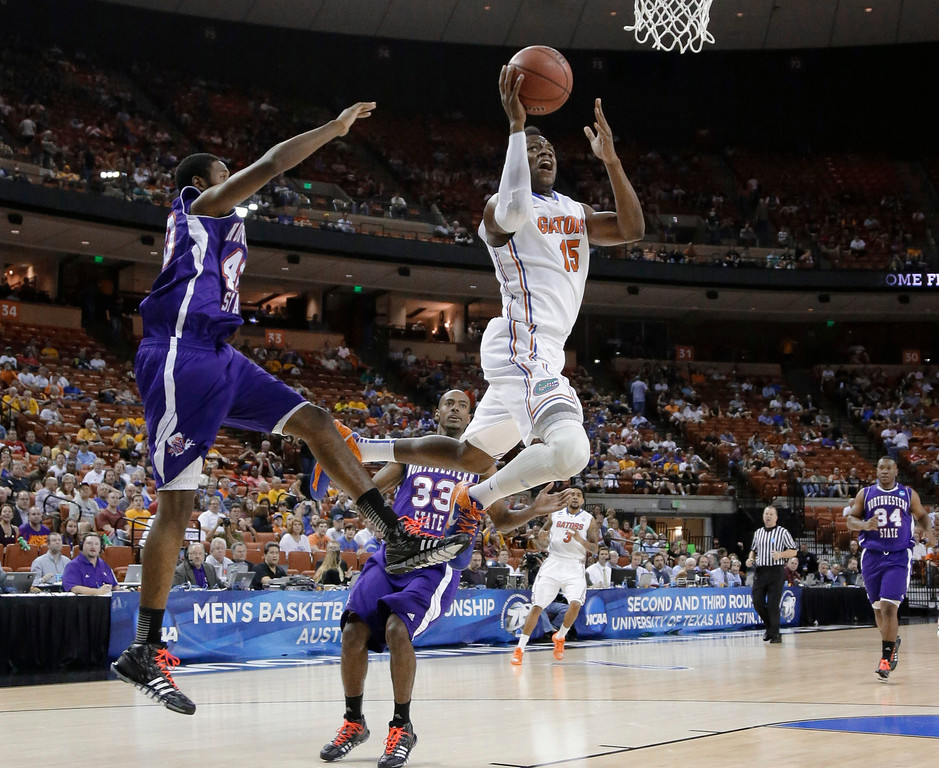 . Florida\'s Will Yeguete (15) drives to the basket past Northwestern State\'s Marvin Frazier, left, during the first half of a second-round game of the NCAA men\'s college basketball tournament Friday, March 22, 2013, in Austin, Texas. (AP Photo/David J. Phillip)