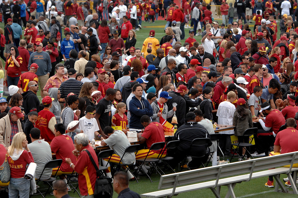 . Fans on the Coliseum field get player\'s autographs following USC\'s Spring Football Game. (Michael Owen Baker/Staff Photographer)