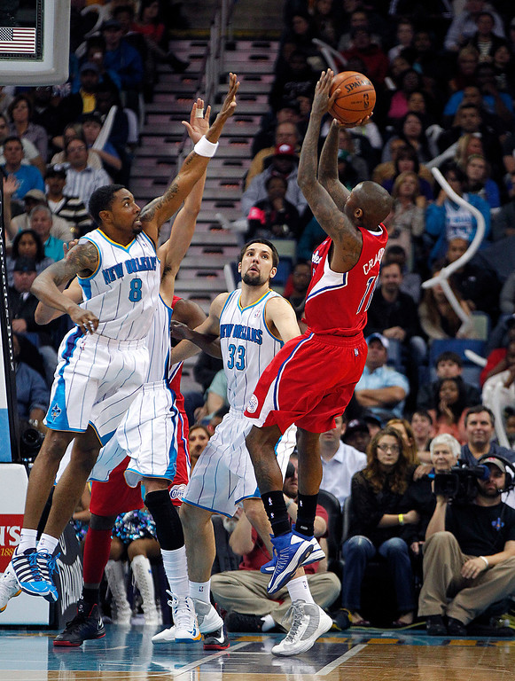 . Los Angeles Clippers shooting guard Jamal Crawford (11) shoots gainst New Orleans Hornets shooting guard Roger Mason Jr. (8) and power forward Ryan Anderson (33) in the second half of an NBA basketball game in New Orleans, Wednesday, March 27, 2013. The Clippers won 105-91. (AP Photo/Gerald Herbert)