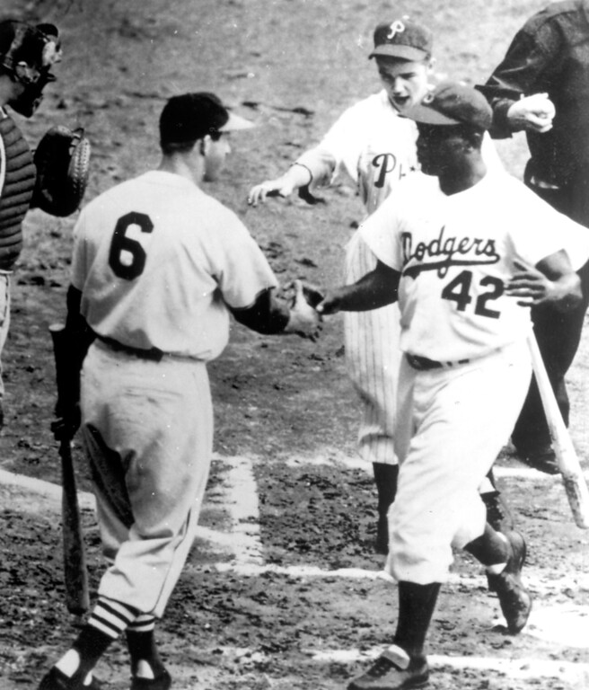 Description of . Jackie Robinson is congratulated by Stan Musial.  Daily News file photo