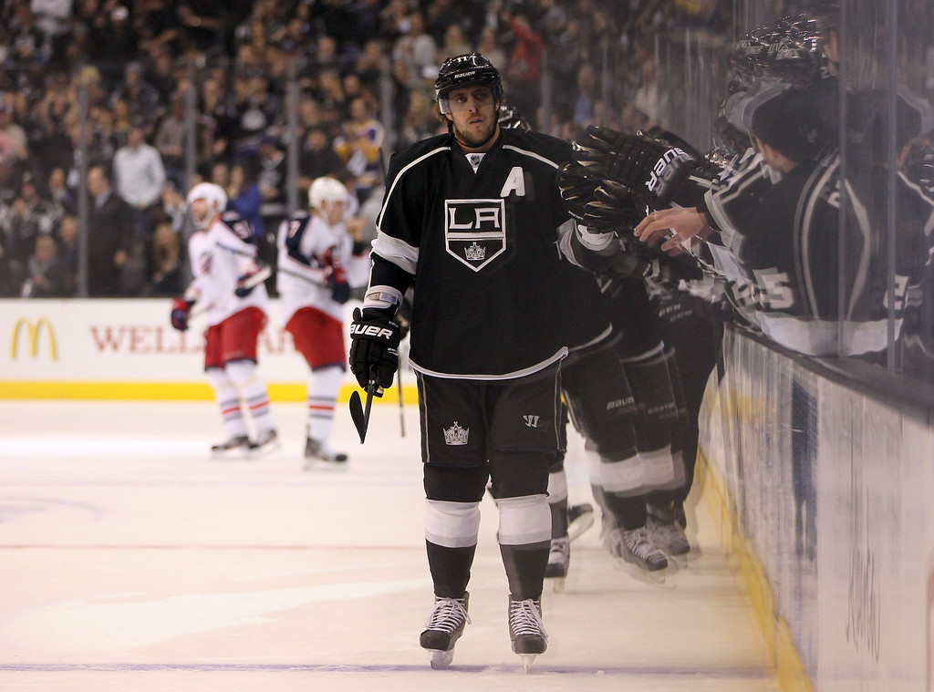 . LOS ANGELES, CA - APRIL 18:  Anze Kopitar #11 of the Los Angeles Kings skates by the bench to celebrate with teammates after a first-period goal by teammate Drew Doughty (not pictured) against the Columbus Blue Jackets during the NHL game at Staples Center on April 18, 2013 in Los Angeles, California. Kopitar assisted on Doughty\'s goal for his 300th career assist. The Kings defeated the Blue Jackets 2-1.  (Photo by Victor Decolongon/Getty Images)