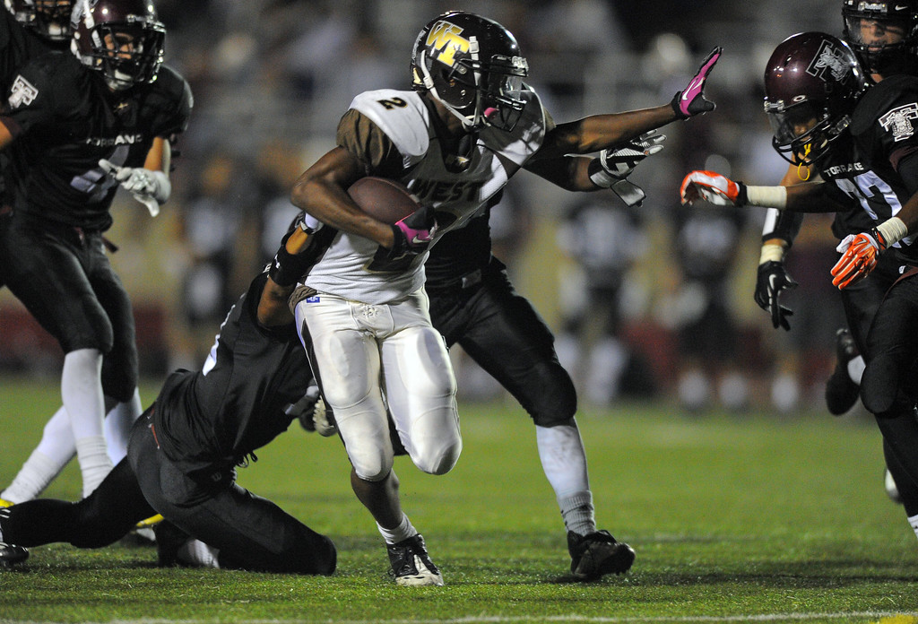 . West High takes on Torrance in a non league football game at Zamperini Stadium in Torrance, CA on Thursday, September 12, 2013. West\'s Brett Ojiyi escapes tackles as he moves up the field. (Photo by Scott Varley, Daily Breeze)