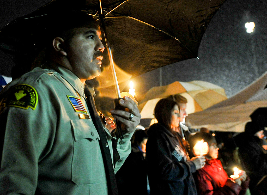 . San Bernardino County Sheriff\'s Deputy Cliff Sanchez holds a candle in the rain during a candlelight vigil in honor of fallen San Bernardino County Sheriff\'s Detective Jeremiah MacKay at the Yucaipa Community Center in Yucaipa, Calif. on Tuesday, Feb. 19, 2013. MacKay was killed by fugitive ex-cop Christopher Dorner on Feb. 12 during a fiery shootout in which Dorner barricaded himself in a cabin near Big Bear. (Rachel Luna / Staff Photographer)