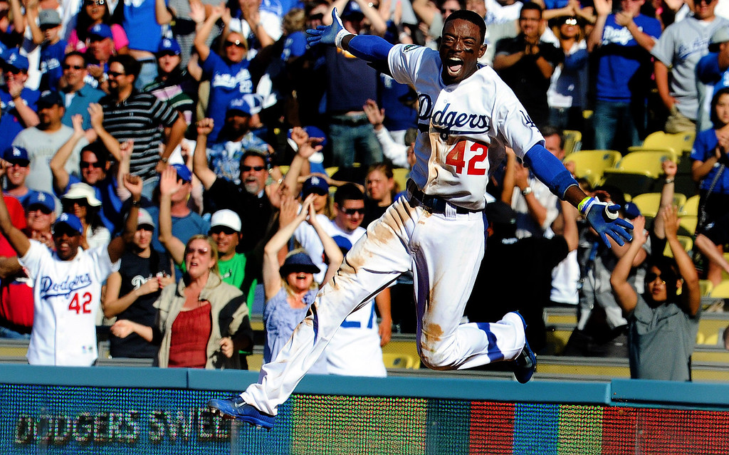 Description of . Los Angeles Dodgers' Dee Gordon reacts after a game winning single with bases loaded as Juan Rivera scores to beat the San Diego Padres 5-4 in the ninth inning of a baseball game in Los Angeles on Sunday, April 15, 2012.  Jackie Robinson's Nephew William Robinson, left, cheers while wearing the number