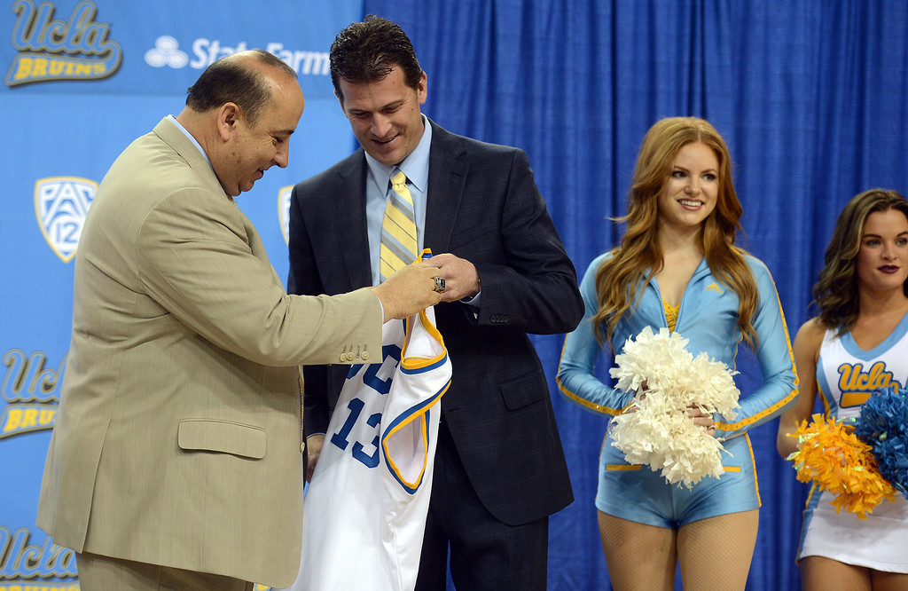 . UCLA athletic director Dan Guerrero gives new men\'s basketball coach Steve Alford a jersey during during a press conference at Pauley Pavillion on the UCLA campus Tuesday, April 2, 2013. (Hans Gutknecht/Staff Photographer)