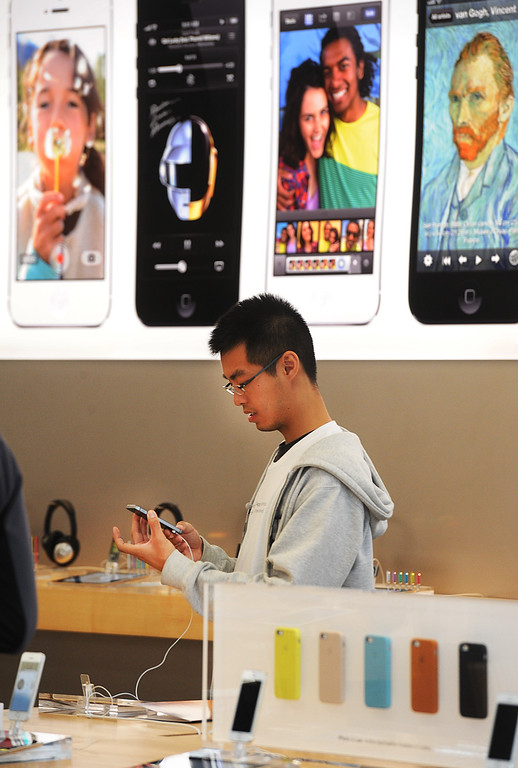 . An Apple customer examines the new IPhone at Apple Store in Pasadena. Long lines of people waited overnight to purchase the newly released IPhones at Apple Store in Pasadena Friday, September 20, 2013. Police detained three people after a fight erupted outside Apple Store, where a crowd waited overnight for release of the new iPhone. The fight was over homeless people who were promised $40 and didn\'t get paid, to wait overnight to purchase IPhones for a buyer.(Photos by Walt Mancini/Pasadena Star-News)