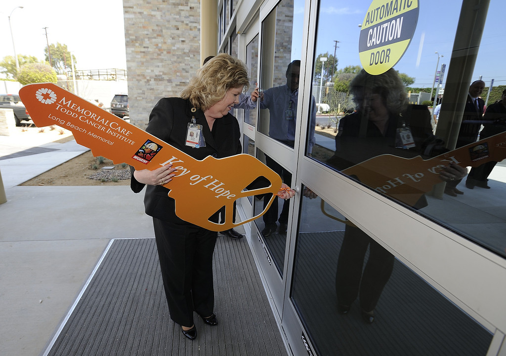 . LONG BEACH, CALIF. USA -- Cathy Kopy, executive director of the Todd Cancer Institute at Long Beach Memorial Medical Center, uses a symbolic key attached to a real key to unlock the new building on April 22, 2013. The new $31 million Todd Cancer Pavilion is scheduled to be unveiled to the public on Saturday, June 29 and open to patients on Monday, July 15. Photo by Jeff Gritchen / Los Angeles Newspaper Group