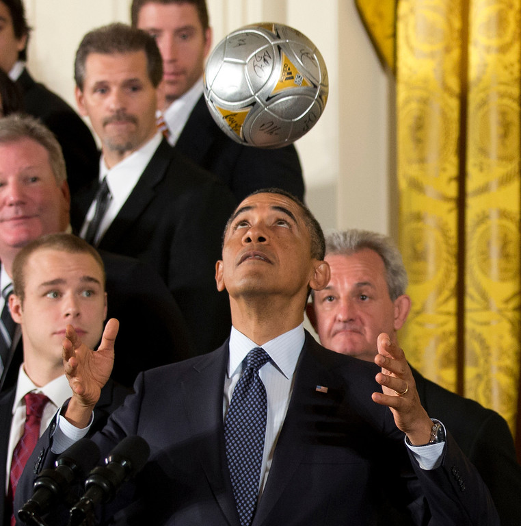 Description of . Los Angeles Kings hockey coach Darryl Sutter, right, and others, watch as President Barack Obama bounces the soccer ball off his forehead during a ceremony  in the East Room of the White House in Washington, Tuesday, March 26, 2013, honoring the Stanley Cup champion Los Angeles Kings and the Major League Soccer champion LA Galaxy for their 2012 championship seasons.   (AP Photo/Manuel Balce Ceneta)