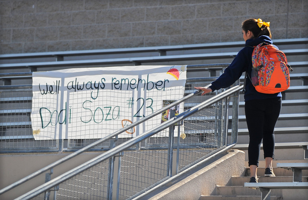 . A Downey High student reads a banner honoring Downey junior varsity football player Dodi Soza Thursday, October 17, 2013. Dodi Soza collapsed on the field after scoring a touchdown and died two days later on Saturday. On the first offensive play of Thursdays game, quarterback Kiefer Enslin carried Soza\'s jersey onto the field and set it on the turf where Soza normally played. Soza\'s brother, Derrick, then went onto the field to retrieve the jersey and brought it to family members.  (Photo by Scott Varley, Daily Breeze)