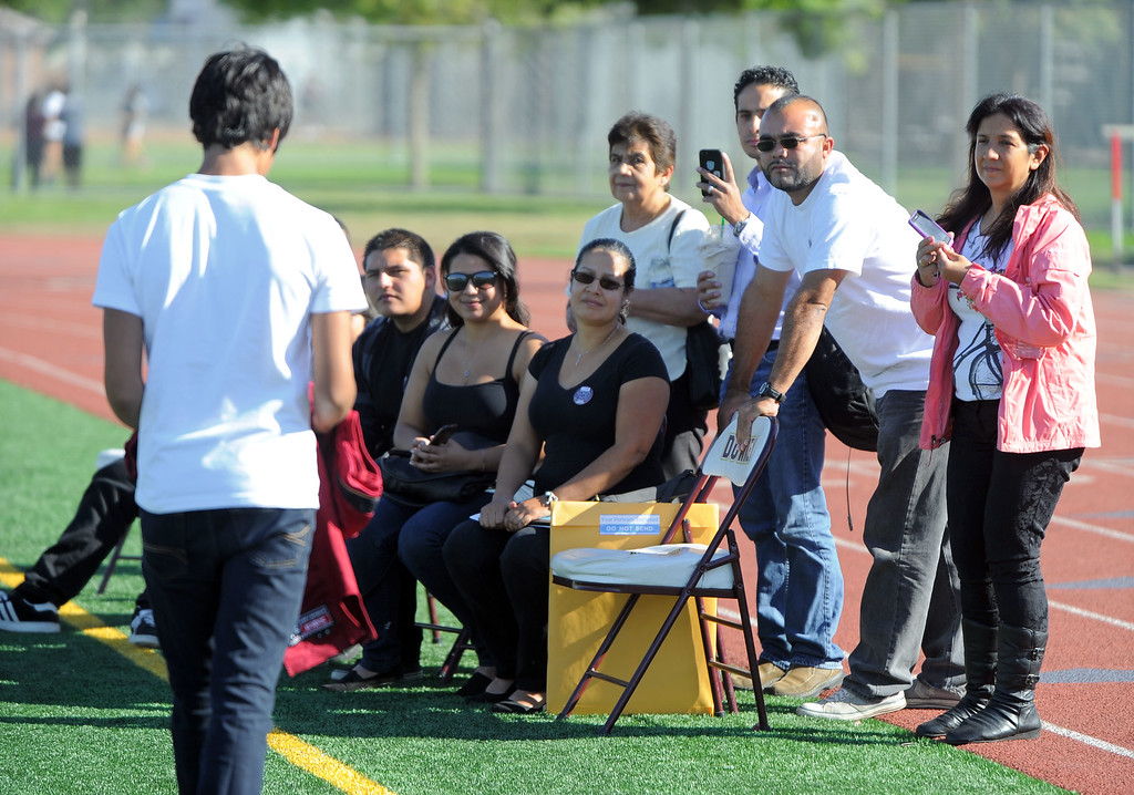 . Family members of Dodi Soza watch as his brother, Derrick, left, brings Dodi\'s jersey to them following a brief tribute to Dodi during the Downey High junior varsity football game against Warren in Downey, CA on Thursday, October 17, 2013. Dodi Soza collapsed on the field after scoring a touchdown and died two days later on Saturday. On the first offensive play of Thursdays game, quarterback Kiefer Enslin carried Soza\'s jersey onto the field and set it on the turf where Soza normally played. Soza\'s brother, Derrick, then went onto the field to retrieve the jersey and brought it to family members.  (Photo by Scott Varley, Daily Breeze)