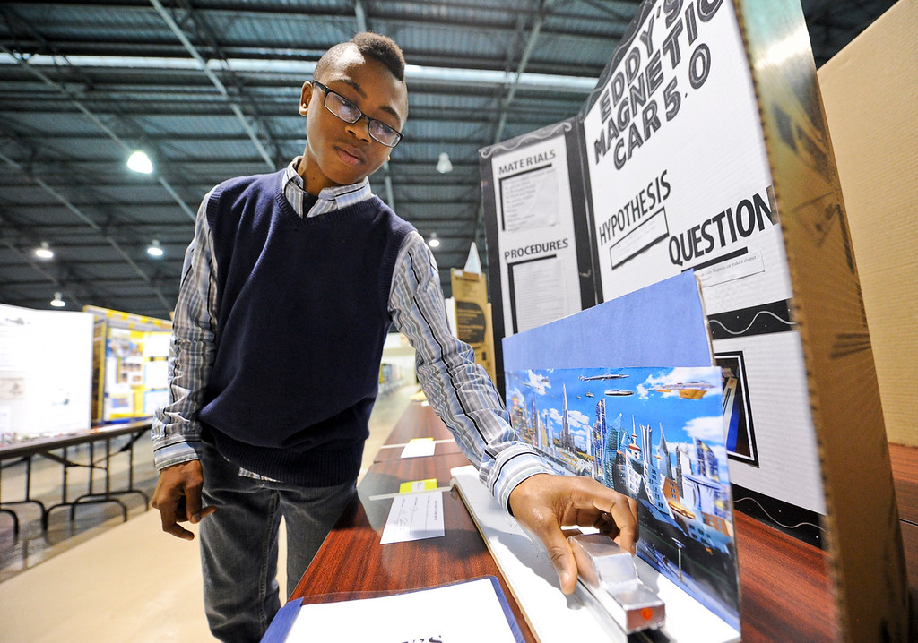 . Lakeside Middle School seventh-grader Jordan Dunlap, 12, of Perris, adjusts his science project display at a science fair hosted at the National Orange Show Events Center in San Bernardino on Tuesday, April 2, 2013. Nearly 940 students from the San Bernardino, Riverside and Inyo counties participated in the event. (Rachel Luna / Staff Photographer)