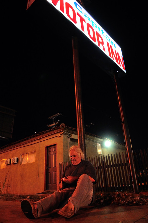 . Tim Grobaty rests under the sign advertising the El Capitan Motor Inn. Photo by Thomas Wasper for the Press Telegram