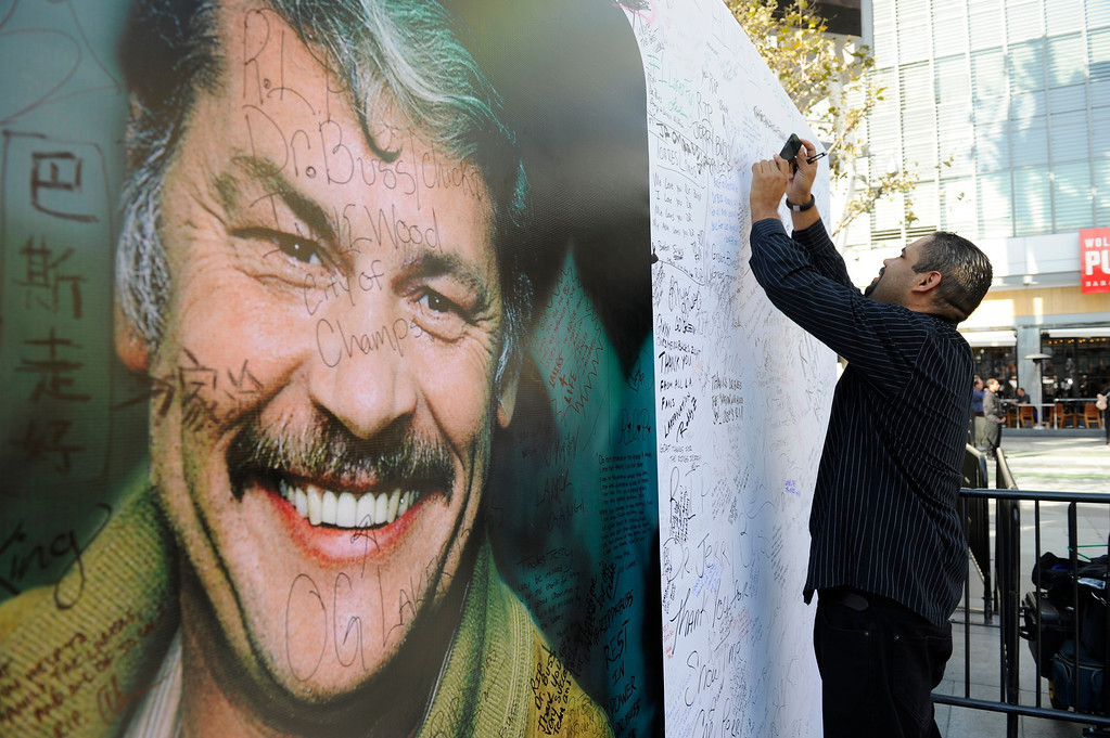 . Albert Stanislaus takes a picture of his signature on a memorial wall of Jerry Buss outside the Jerry Buss Memorial Service at Nokia Theatre, Thursday, February 21, 2013. (Michael Owen Baker/Staff Photographer)