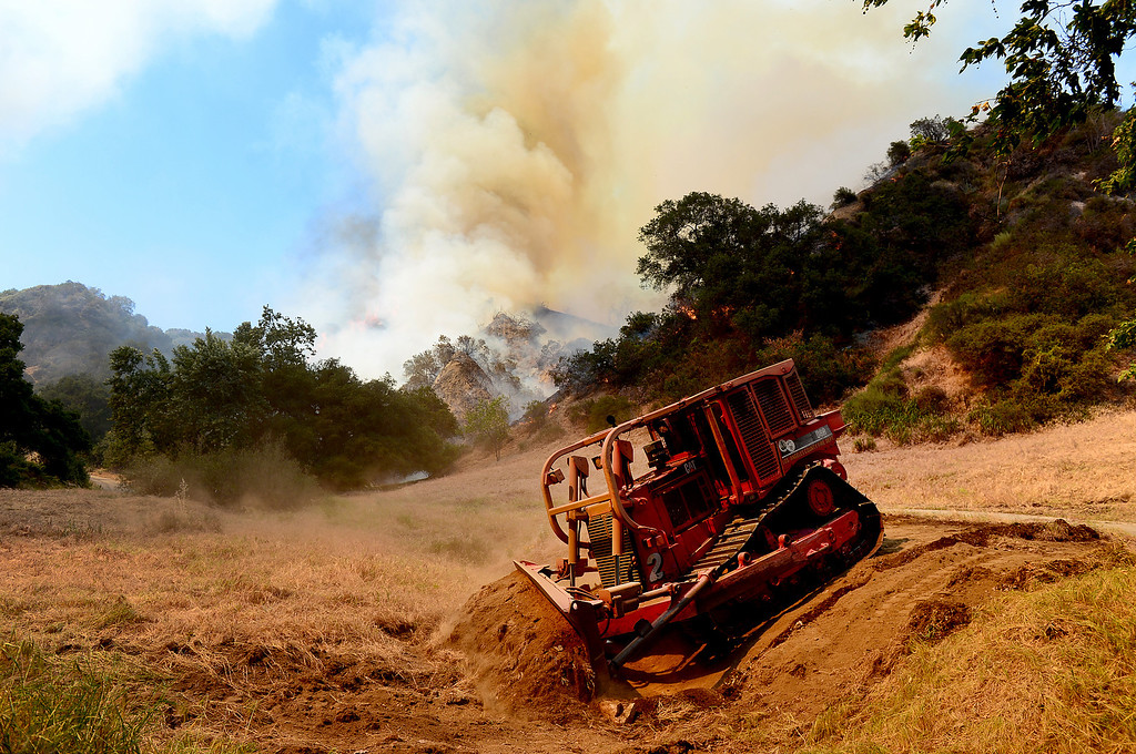 Description of . LA County Fire cuts a fire line as they battle a fast spreading brush fire in Monrovia that is believed to have been sparked by gardening work on Madison Avenue Saturday April 20, 2013. (SGVN/Staff Photo by Sarah Reingewirtz)