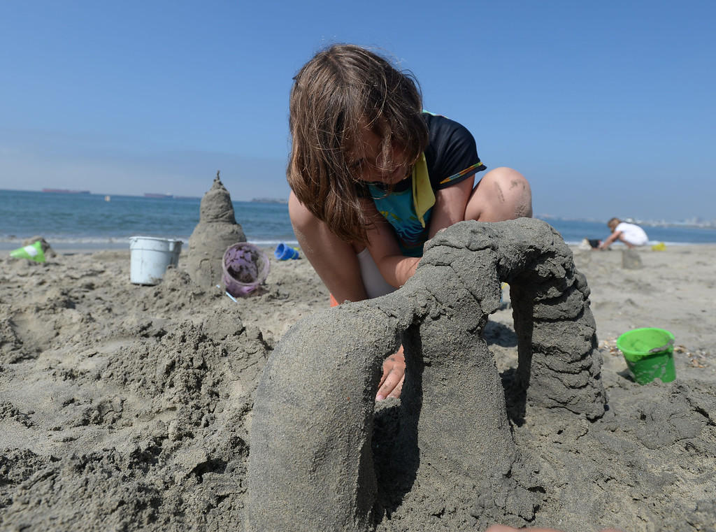 . Children had a chance to hone their sand castle building skills in a sand castle camp Monday at Granada Beach in Belmont Shore. Kathryn Sheridan adds to a double arch while trying to keep it from collapsing. 20130805 Photo by Steve McCrank / Staff Photographer