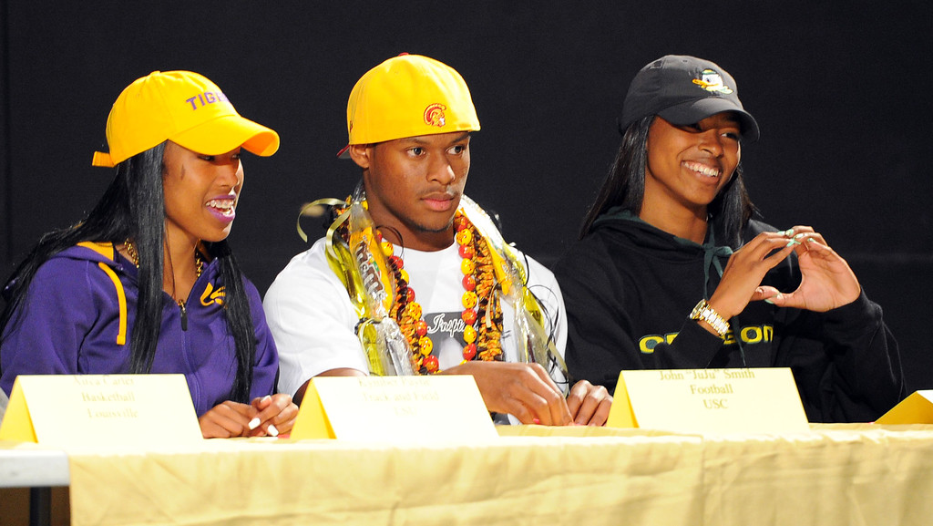 """. From left, Kymber Payne (LSU track), John \""""JuJu\"""" Smith (USC football) and Ariana Washington (Oregon track) get ready to sign their national letters of intent during a ceremony in Long Beach, CA on Wednesday, February 5, 2014. 18 students athletes at Long Beach Poly signed their national letters of intent to play athletics at 4-year universities. (Photo by Scott Varley, Daily Breeze)"""