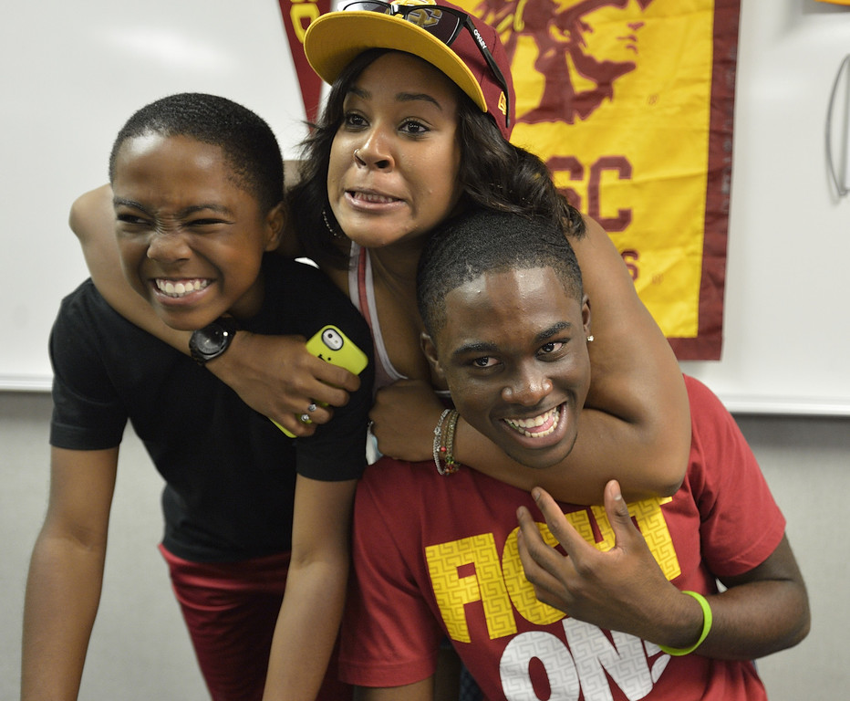 . LAKEWOOD, CALIF. USA -- Destinee Minor jokes with her little brothers, Cameron Minor, left, and Mayfair High recent graduate Aaron Minor, during his Signing Ceremony in Lakewood, Calif., on July 2, 2013. Minor is a late signee with USC football. Photo by Jeff Gritchen / Los Angeles Newspaper Group