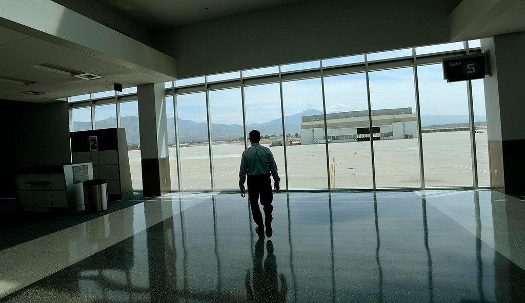 Description of . Airport Manager Scott Gibbs walks towards a window overlooking the tarmac of the San Bernardino International Airport March 28, 2013.  Built on the former the site of the former Norton Air Force Base, is often described by local officials as one of the East Valley's best hopes for economic growth. Norton closed in 1994.  GABRIEL LUIS ACOSTA/STAFF PHOTOGRAPHER.