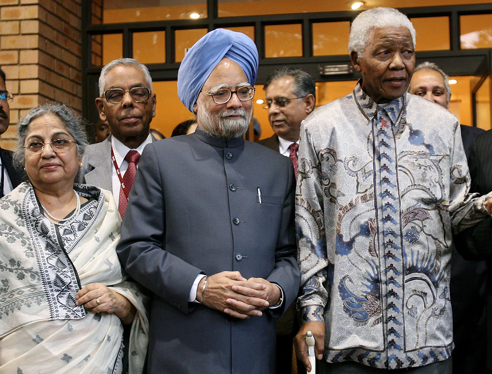 ". Indian Prime Minister Manmohan Singh, center, and his wife Kaur, left,  pose for photographers with former South African president Nelson Mandela after their meeting at the Mandela foundation in Johannesburg Monday Oct. 2, 2006. Singh on Monday paid tribute to former president Nelson Mandela, calling him the ""greatest Gandhian\"" of all time.   (AP Photo/Jerome Delay)"