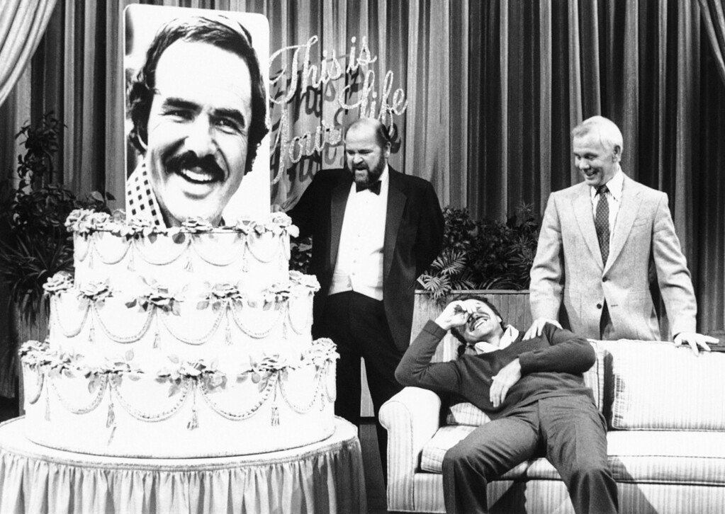 . Burt Reynolds breaks into laughter as host Johnny Carson, right, and friend and fellow actor Dom De Luise present Reynolds with a 46th birthday cake, complete with enlarged photo of himself inside, during NBC?s ?The Tonight Show? in Burbank  Thursday, Feb. 12, 1982. The birthday party and the skit, ?This Is Your Life,? were a surprise to Reynolds from the show?s staff. (AP Photo)